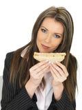 吃年轻的女商人拿着一条黑面包健康三文鱼用黄瓜三明治 库存图片