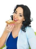 吃整粒薄脆饼干用嘎吱咬嚼的花生酱和切的香蕉的少妇 免版税库存图片