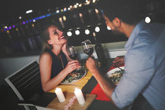 吃年轻美好的夫妇在屋顶的浪漫晚餐 免版税库存图片