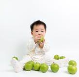 吃绿色苹果的亚裔婴孩 免版税库存图片