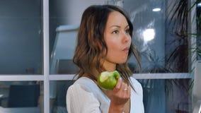 吃绿色苹果的俏丽的女实业家在办公室 免版税库存图片