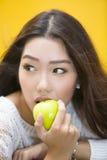 吃绿色苹果的妇女 库存图片