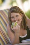吃绿色苹果计算机的愉快的妇女 免版税库存图片