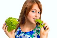 吃莴苣的美丽的女孩 库存照片