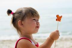 吃蝴蝶棒棒糖的女婴 免版税库存照片
