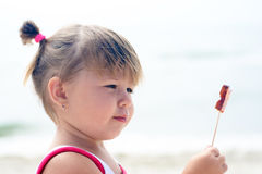 吃蝴蝶棒棒糖的女婴 库存图片