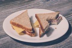 吃dieitng鲜美自创三明治的不健康的快速的破烂物 关闭在一块圆的板材的鲜美被咬住的乳酪三明治 木后面 免版税库存照片
