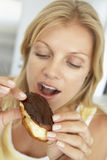 吃eclair中间妇女的成人巧克力 免版税库存图片