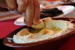 吃Hummus用皮塔饼面包 免版税库存图片