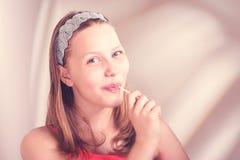 吃lollypop的滑稽的青少年的女孩 免版税图库摄影