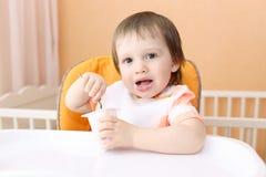 吃youghourt的可爱的婴孩 免版税库存照片