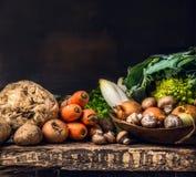 各种各样未加工的蔬菜和领域蘑菇在老黑暗木 免版税图库摄影