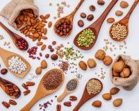 各种各样的亲切的豆类和坚果壳在匙子和大麻袋装袋子 库存图片