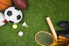 各种各样的体育球、棒球棒和手套,在绿色草坪的羽毛球拍 免版税库存照片