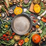 各种各样的健康和有机收获菜和成份:南瓜,绿色,蕃茄,无头甘蓝,韭葱,唐莴苣,在空的cooki附近的芹菜 免版税库存照片