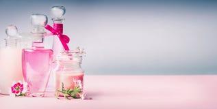 各种各样的化妆在桃红色桌书桌上的产品玻璃瓶在灰色背景,正面图,横幅 库存照片