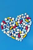 各种各样的医学药片在心脏形状垂直安排了 库存照片