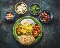 各种各样的印地安食物滚保龄球用咖喱、酸奶、米、面包、酸辣调味品、paneer乳酪和香料在黑暗的土气背景 免版税库存照片