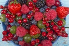 各种各样的在一个碗的夏天新鲜的莓果在土气木桌上 抗氧剂,戒毒所饮食,有机果子 顶视图 库存照片