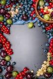 各种各样的夏天莓果框架在土气背景的 库存照片