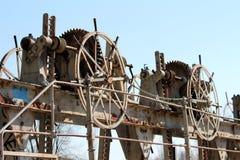 各种各样的大小钝齿轮生锈了齿轮在被放弃的水坝锁以小链子防止未批准的用法 免版税库存照片