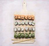 各种各样的寿司设置,莳萝,三文鱼,在白色切板亚洲食物的螃蟹在木土气背景顶视图关闭 免版税库存照片