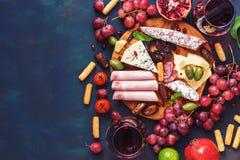 各种各样的开胃菜红色酒,果子,香肠,乳酪,在黑暗的finem背景的菜 复制空间,顶视图 库存图片