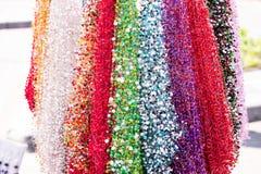 各种各样的形状和颜色不同的项链与色的石头在被弄脏的背景 库存图片