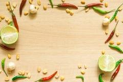 各种各样的新鲜蔬菜辣椒粉、花生、在木背景和草本顶视图隔绝的大蒜、柠檬 免版税库存图片
