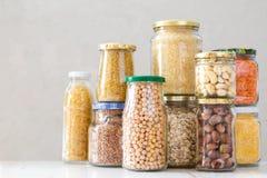 各种各样的未煮过的谷物、五谷、豆和面团健康烹调的在玻璃瓶子 免版税库存图片