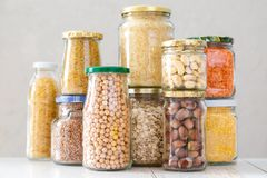 各种各样的未煮过的谷物、五谷、豆和面团健康烹调的在玻璃瓶子 库存图片