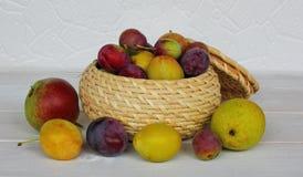 各种各样的李子和梨在一个柳条罐 库存图片