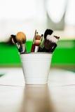 各种各样的构成刷子和铅笔在浅绿色的背景在桶里面地板 Copyspace 免版税图库摄影