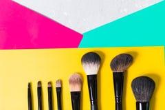 各种各样的构成刷子在明亮的黄色,桃红色,绿色背景,特写镜头,化妆用品中 免版税库存图片