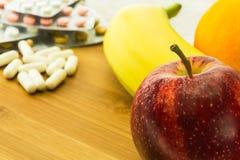 各种各样的果子和维生素药片 免版税库存照片