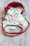 各种各样的欧洲钞票从红色提包下降  库存照片