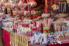 各种各样的甜点、糖果和棒棒糖在街市上 免版税库存照片