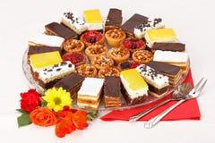 各种各样的甜点在圆的板材结块 库存图片