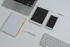 各种各样的电子小配件和书在白色背景 免版税图库摄影