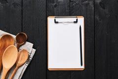 各种各样的盘的食物背景与clipboar空白的纸板 免版税库存图片
