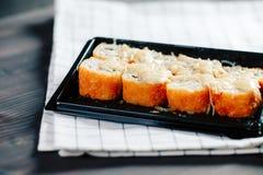 各种各样的种类热的油煎的卷在桌上的塑料寿司箱子服务 图库摄影