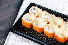 各种各样的种类热的油煎的卷在桌上的塑料寿司箱子服务 免版税库存图片