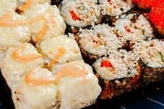 各种各样的种类热的油煎的寿司卷在桌上服务 宏观射击 图库摄影