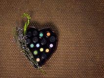 各种各样的精油,装瓶在小瓶和安排在与淡紫色分支的一心形,在编辫子的酒椰安置了 库存照片