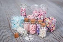 各种各样的糖果在微小的存贮案件洒 库存照片