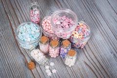 各种各样的糖果在微小的存贮案件洒 免版税图库摄影