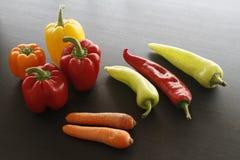 各种各样的胡椒和红萝卜在木桌上 图库摄影