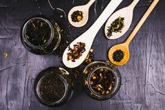 各种各样的茶、香料和果子在黑暗的织地不很细背景 库存图片