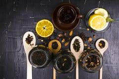 各种各样的茶、香料和果子在黑暗的织地不很细背景 图库摄影
