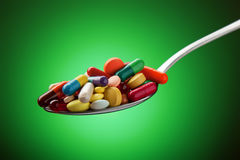 各种各样的药片、在匙子堆积的胶囊和片剂 库存照片